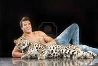 black naked man zigf young man naked torso sits near spotty leopard black background photo